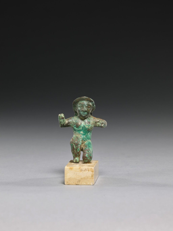A GREEK BRONZE KNEELING FIGURE, LATE 6TH CENTURY B.C.