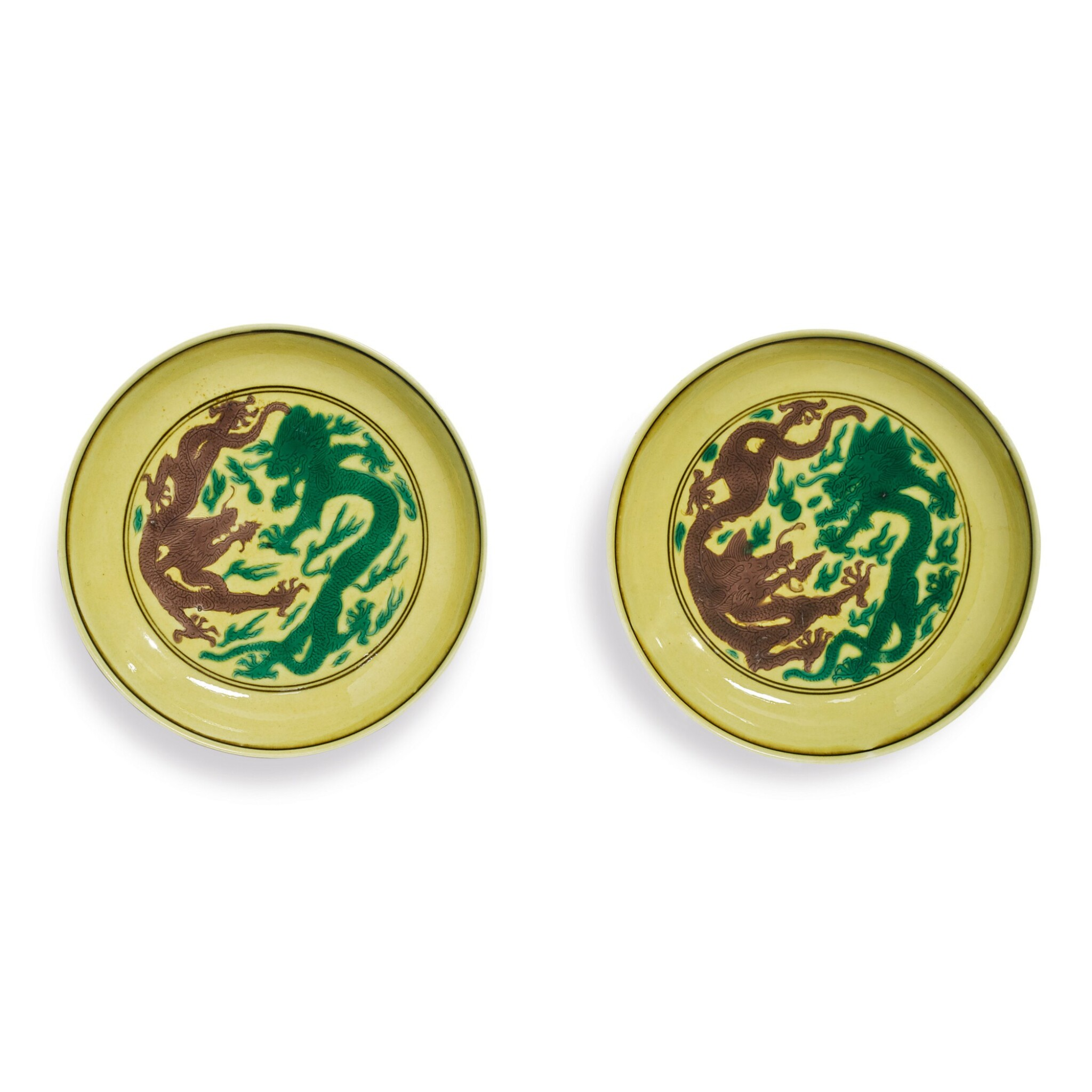 View full screen - View 1 of Lot 559. A PAIR OF GREEN AND AUBERGINE-ENAMELED YELLOW-GROUND 'DRAGON' DISHES,  KANGXI MARKS AND PERIOD.