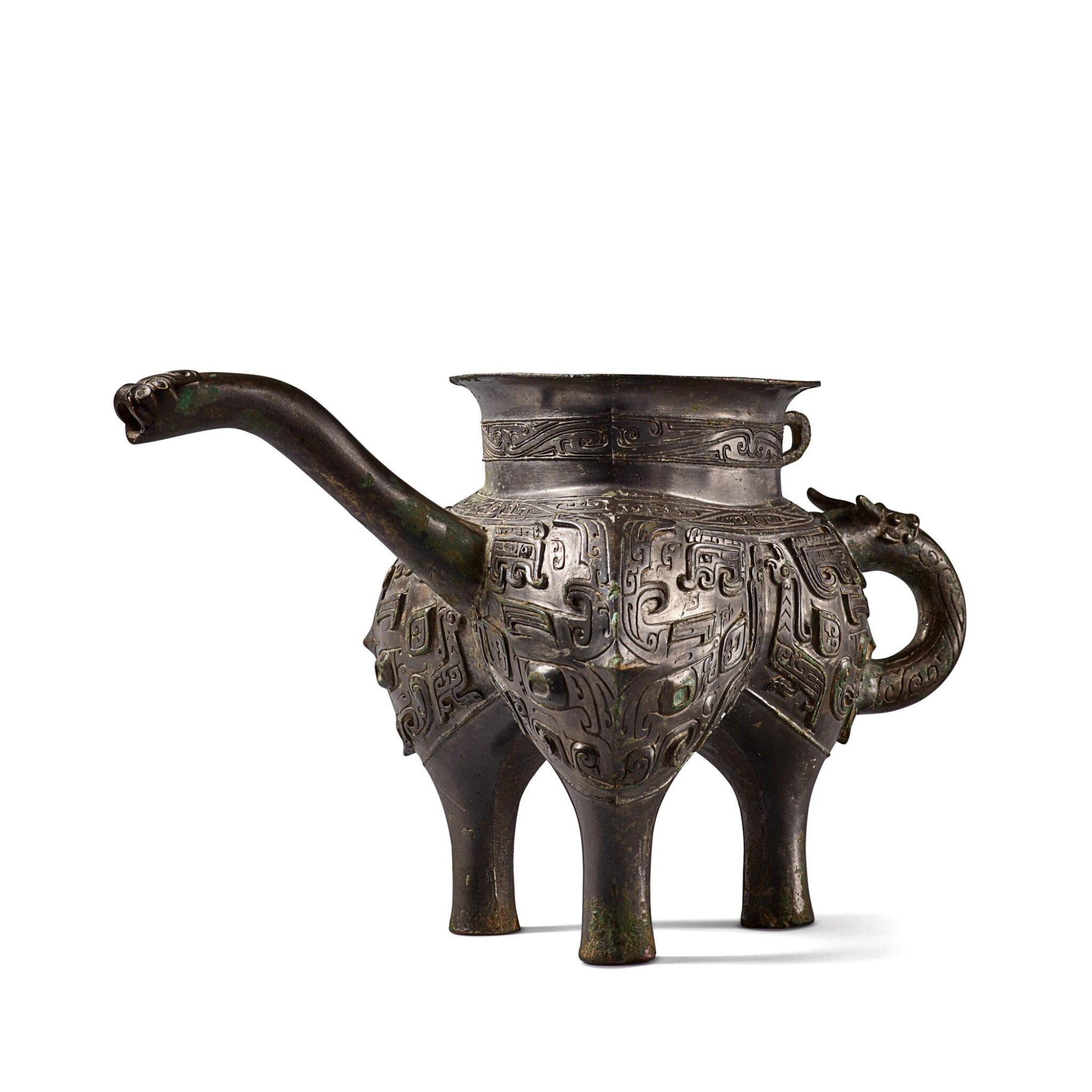 View full screen - View 1 of Lot 12. An exceptionally rare archaic bronze ritual pouring vessel (He), Eastern Zhou dynasty, Spring and Autumn period | 東周 春秋 青銅獸面紋龍流盉.