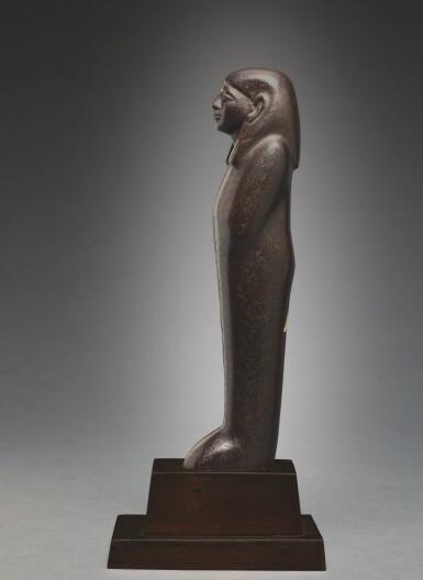 View 5. Thumbnail of Lot 66. AN EGYPTIAN BROWN SERPENTINE USHABTI OF NEDJEM-IB, LATE 12TH/13TH DYNASTY, CIRCA 1800-1640 B.C..