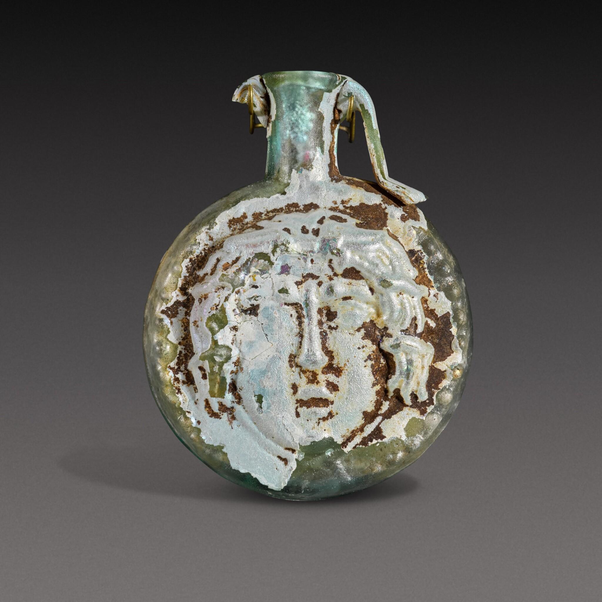View full screen - View 1 of Lot 1. A Roman Pale Green Mould-Blown Janiform Glass Flask, circa 1st/2nd century A.D..