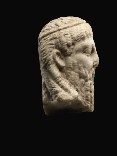 A ROMAN MARBLE ARCHAISTIC HERM HEAD OF DIONYSOS, CIRCA 2ND CENTURY A.D.
