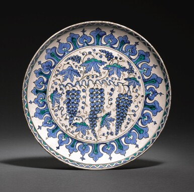 AN IZNIK POTTERY RIMLESS 'GRAPE' DISH, TURKEY, CIRCA 1570-80
