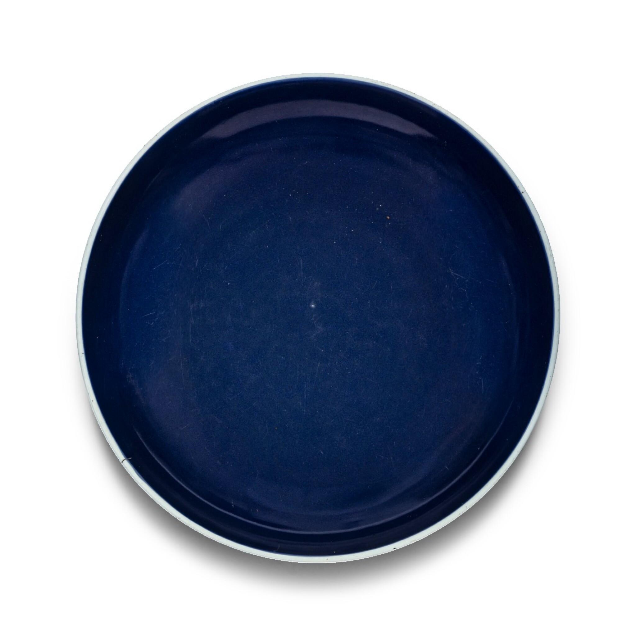 View 1 of Lot 17. Grand plat en porcelaine monochrome bleu Dynastie Qing, XVIIIE siècle   清十八世紀 灑藍釉圓盤   A large sacrificial blue-glazed charger, Qing Dynasty, 18th century.