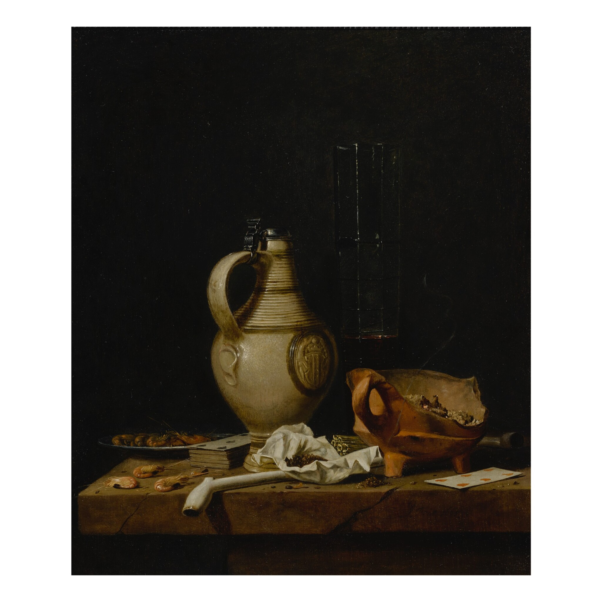 A still life with a stoneware jug, a glass of beer, playing cards and smokers' requisites