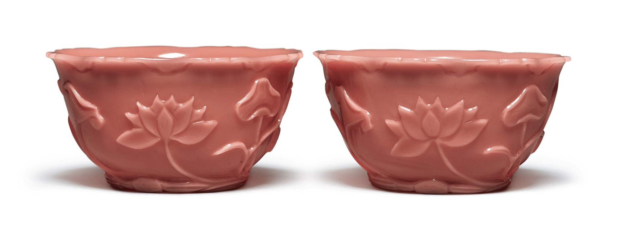 View 1 of Lot 1017. A PAIR OF CARVED PINK GLASS 'LOTUS' BOWLS, QING DYNASTY, 19TH CENTURY.