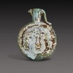 A Roman Pale Green Mould-Blown Janiform Glass Flask, circa 1st/2nd century A.D.