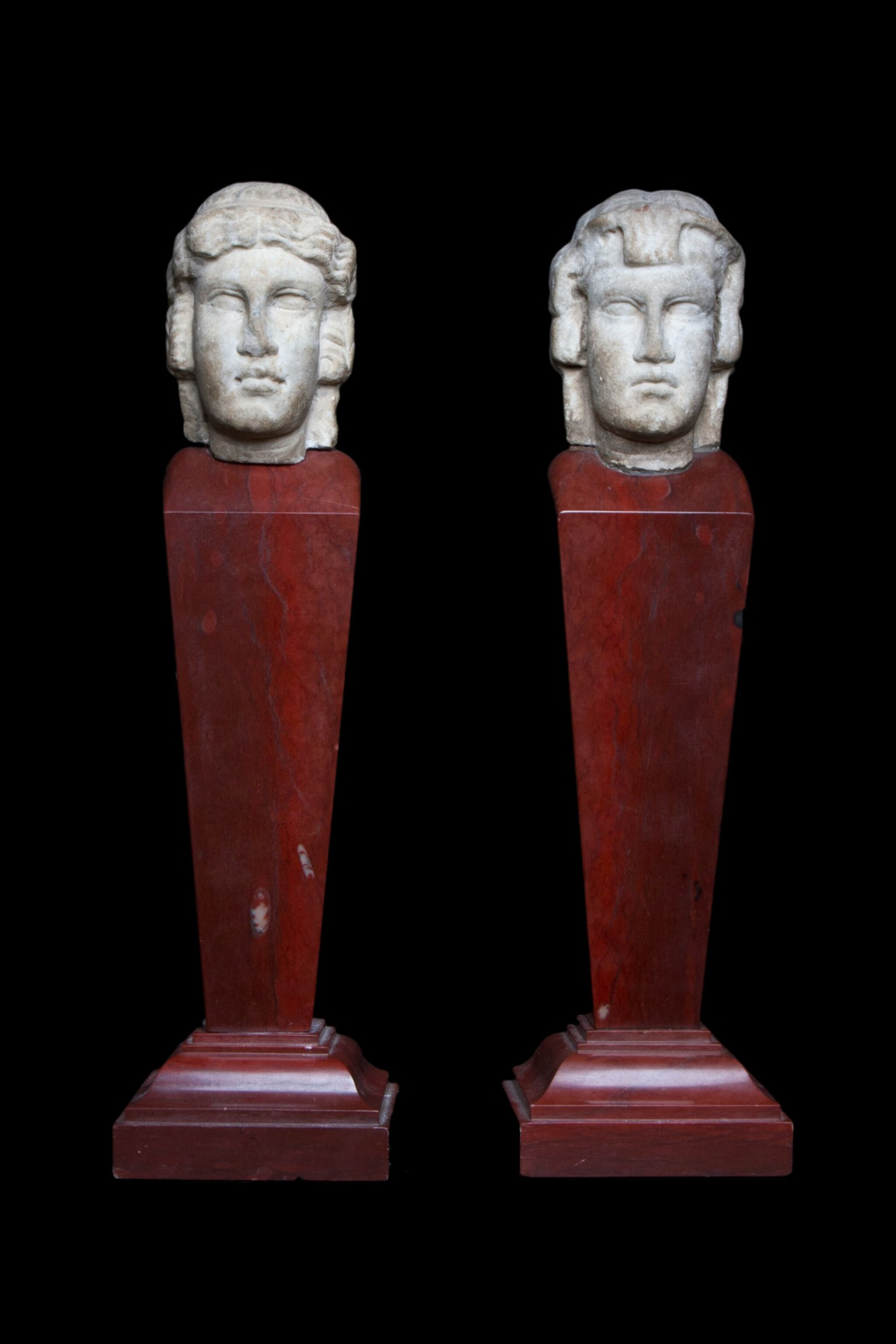 View 1 of Lot 97. Two Roman Marble Janiform Herm Heads, circa 2nd century A.D., mounted as a pair on red marble shafts, probably in the 19th Century, circa 1st Century A.D..