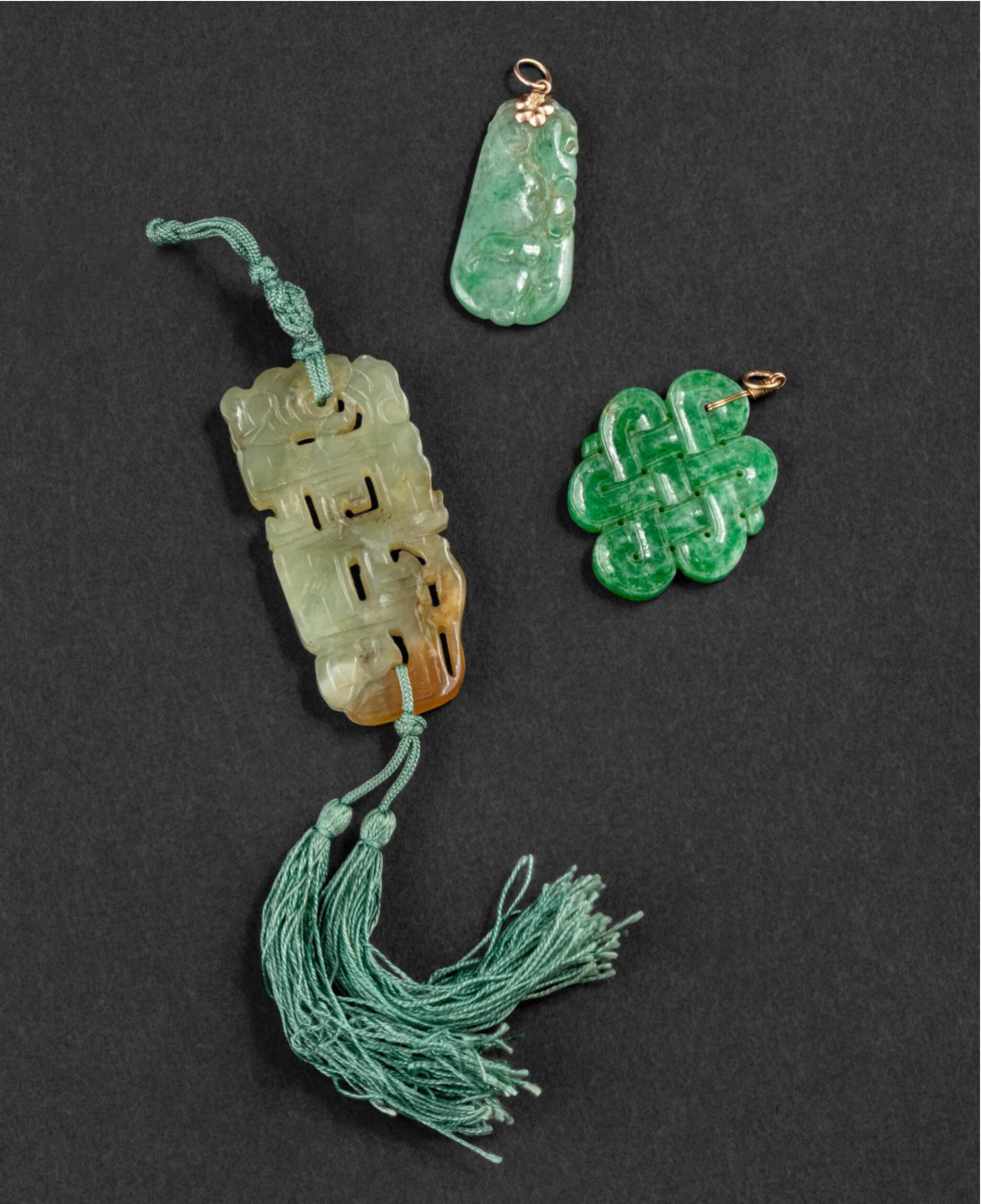 View 1 of Lot 65. Ensemble de trois pendentifs sculptés en jade et en jadéite XIXE-XXE siècle   十九至二十世紀 玉珮 一組三件   A group of three céladon jade and jadeite pendants, 19th-20th century.