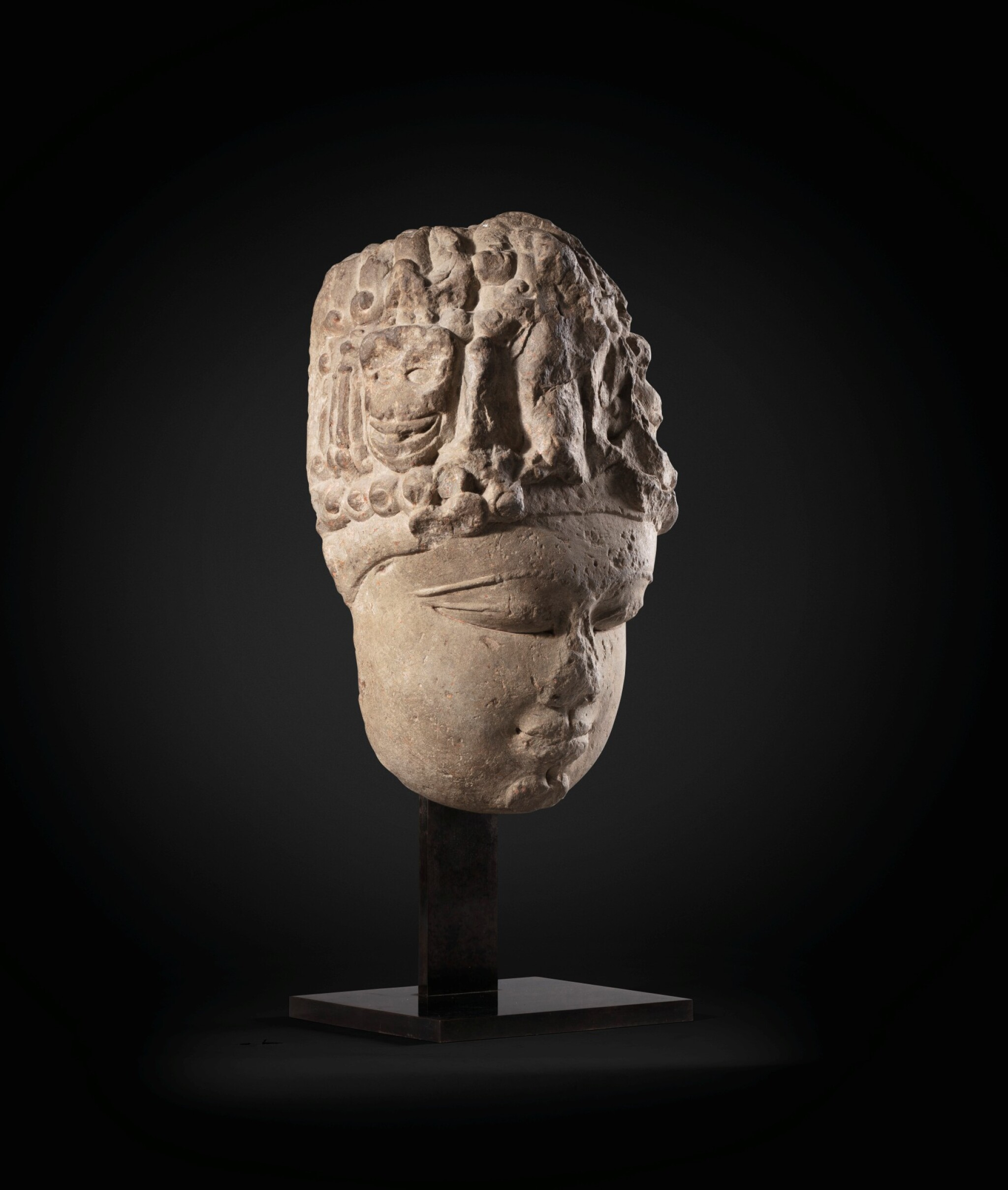 View full screen - View 1 of Lot 243. A monumental buff sandstone head of a Devi North India, 9th-10th century | 印度北部 九至十世紀 砂岩雕提毗首.