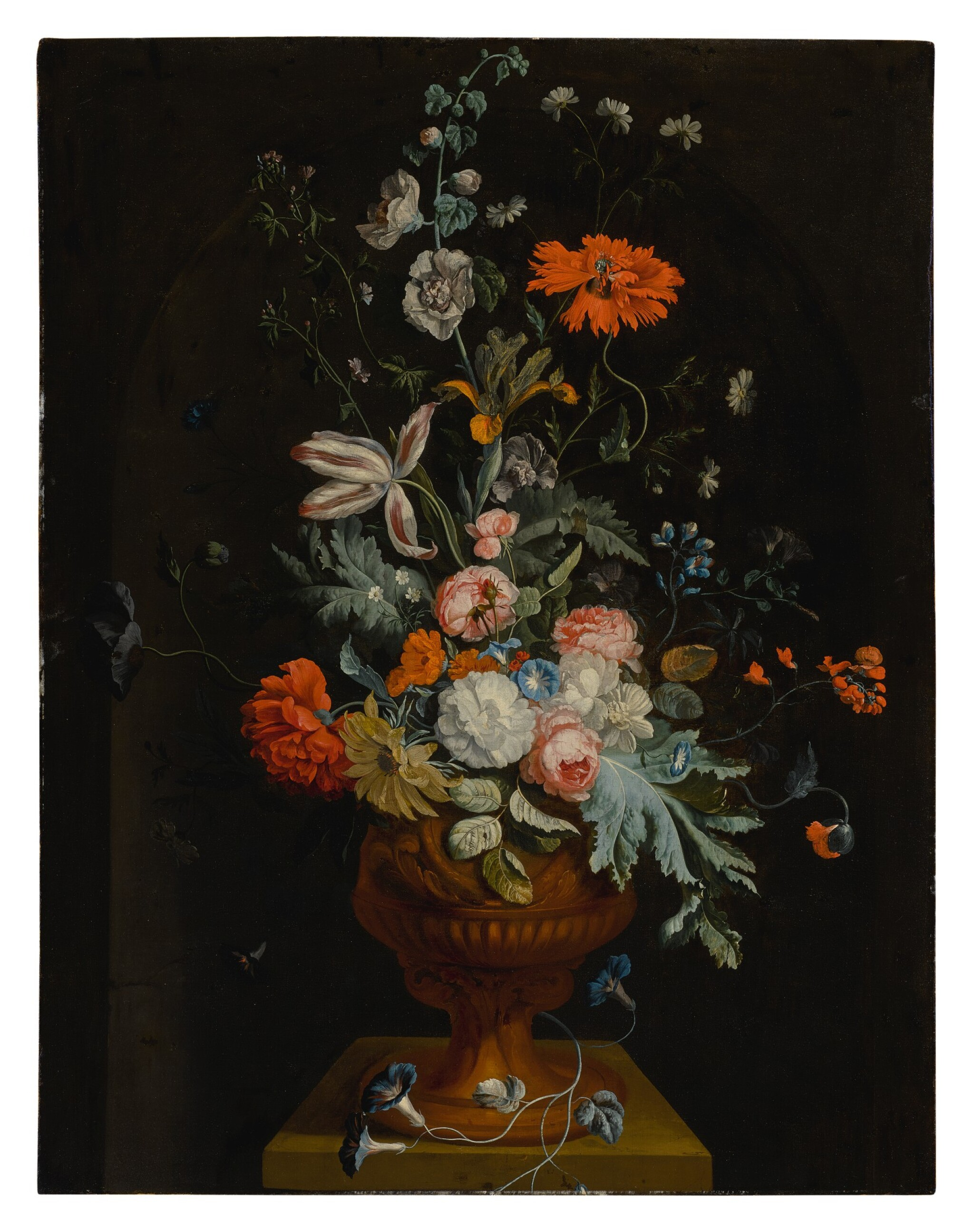 Still life of flowers in a terracotta vase before a stone niche