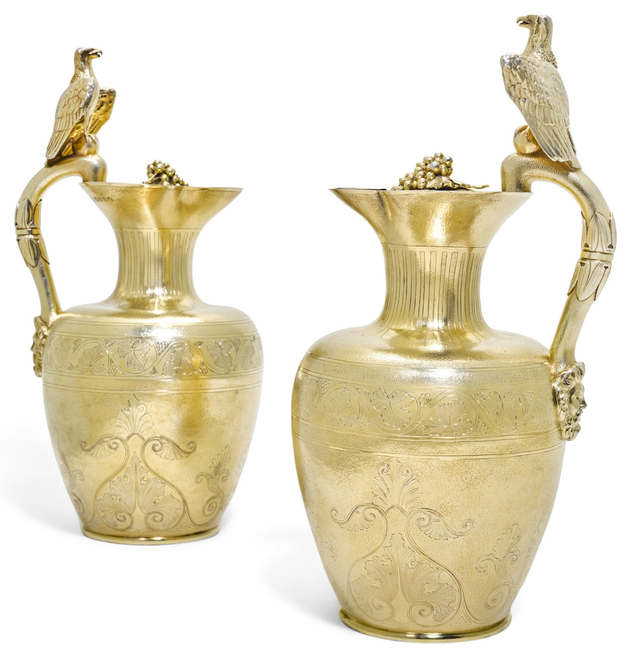 View full screen - View 1 of Lot 139. ROYAL. A PAIR OF WILLIAM IV SILVER-GILT CLARET JUGS, ONE JOHN BRIDGE FOR RUNDELL, BRIDGE & RUNDELL, 1833, THE OTHER JOHN SPARKES TAPLEY FOR JOHN TAPLEY & CO., 1835, BOTH LONDON, RETAILED BY RUNDELL, BRIDGE & CO..