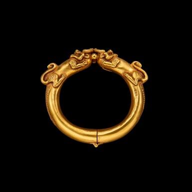 View 1. Thumbnail of Lot 1030. A gold 'mythical beast' bangle Possibly Sumatra, Indonesian archipelago, 19th century | 十九世紀 或印尼群島蘇門答臘 雙獸首金鐲.