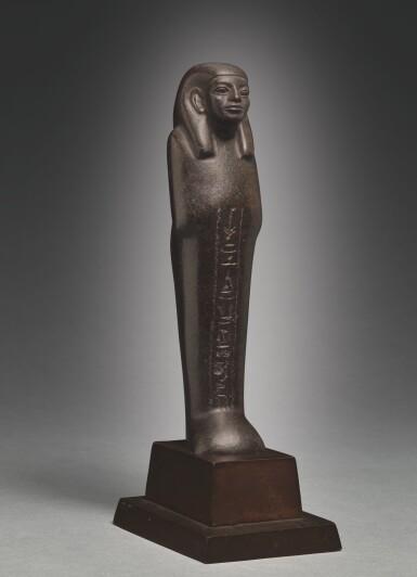 View 2. Thumbnail of Lot 66. AN EGYPTIAN BROWN SERPENTINE USHABTI OF NEDJEM-IB, LATE 12TH/13TH DYNASTY, CIRCA 1800-1640 B.C..