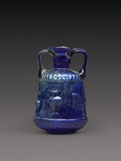 View 1. Thumbnail of Lot 3. A Roman Cobalt Blue Mould-Blown Glass Amphoriskos, circa 1st century A.D..