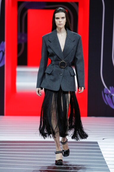 View 8. Thumbnail of Lot 13. PRADA   OPENING LOOK OF THE SHOW.  FLUID FRINGE DRESS, WOOL JACKET, VANITY BELT, BRUSHED LEATHER PUMPS, WORN BY MEGHAN COLLISON.