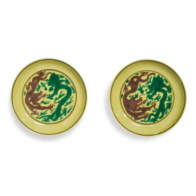 View 1. Thumbnail of Lot 559. A PAIR OF GREEN AND AUBERGINE-ENAMELED YELLOW-GROUND 'DRAGON' DISHES,  KANGXI MARKS AND PERIOD.