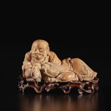 View 3. Thumbnail of Lot 671. A BEIGE SOAPSTONE FIGURE OF A RECLINING LUOHAN, 17TH / 18TH CENTURY.