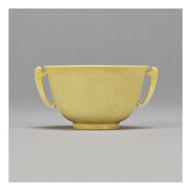 A FINE INCISED YELLOW-GLAZED 'DRAGON' HANDLED CUP,  KANGXI MARK AND PERIOD