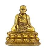 A GILT-BRONZE FIGURE OF A LAMA,  TIBET, 13TH – 14TH CENTURY   十三至十四世紀 藏傳鎏金銅喇嘛坐像