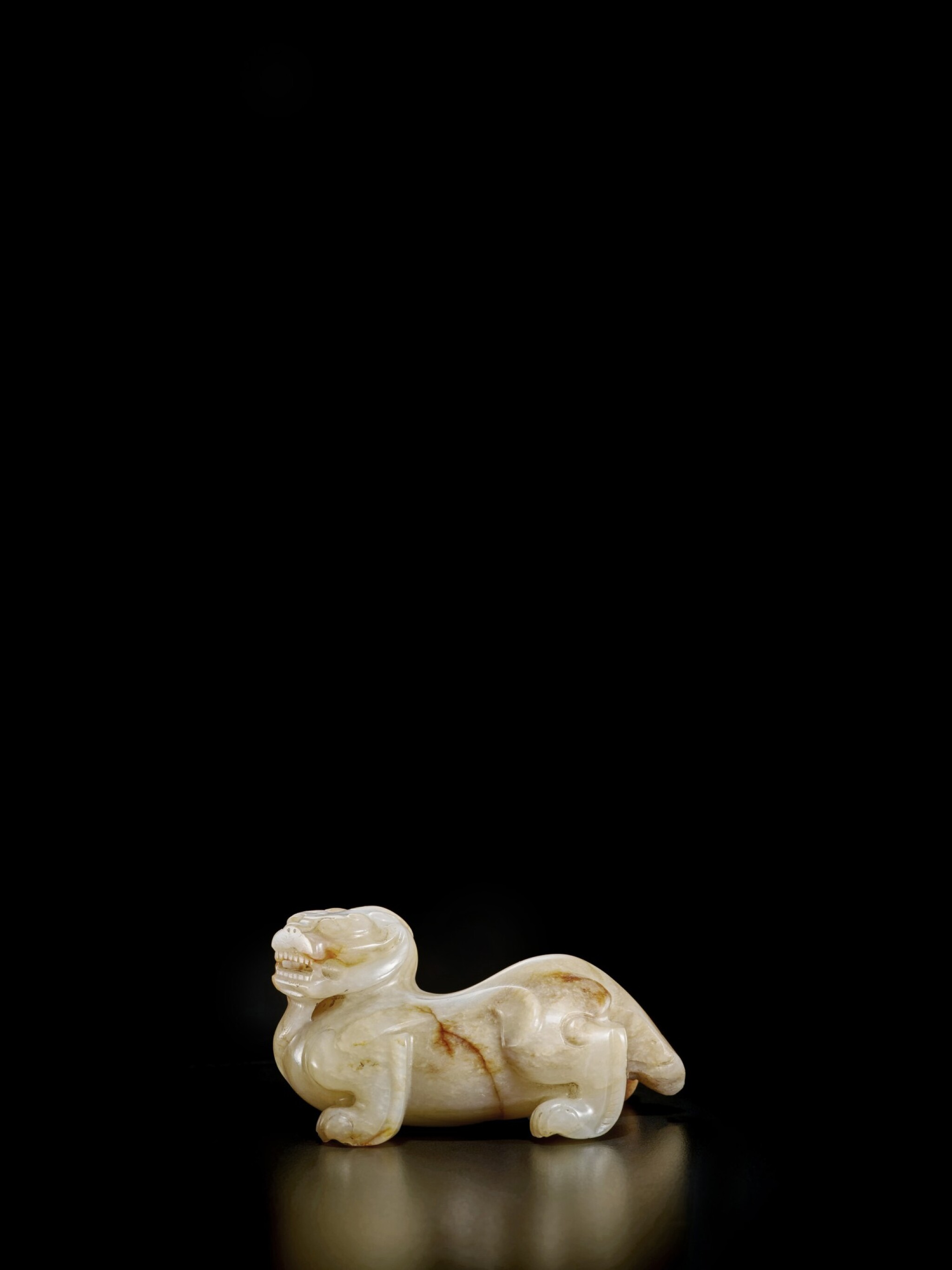 View full screen - View 1 of Lot 46. A beige and russet jade bixie, Han - Six Dynasties | 漢至六朝 玉辟邪.