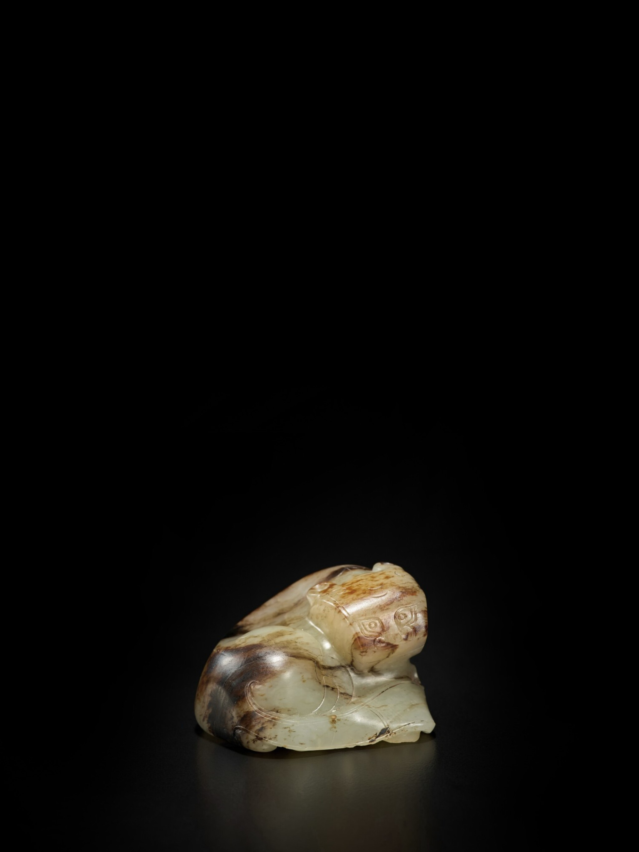 View full screen - View 1 of Lot 52. A pale green and brown jade figure of a tiger, Ming dynasty | 明 玉臥虎.