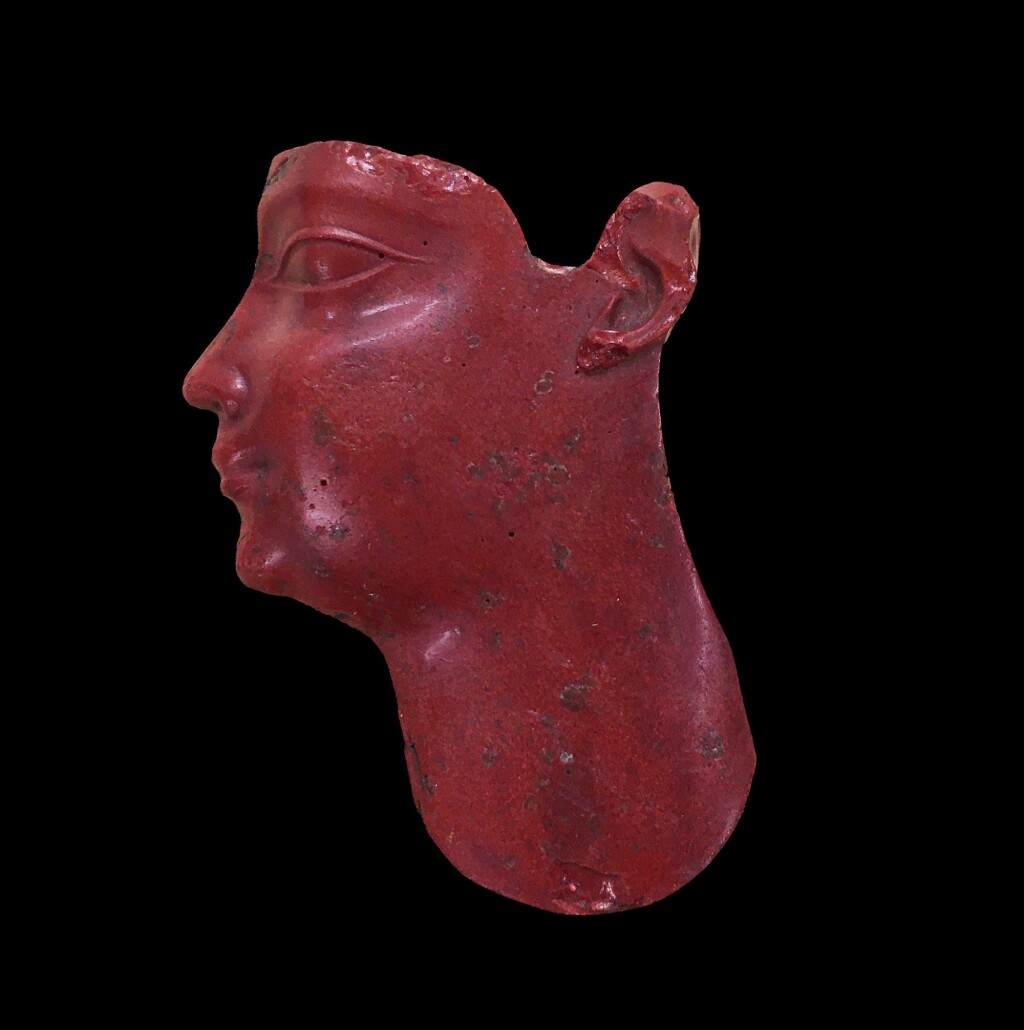 AN EGYPTIAN RED GLASS INLAY HEAD, 30TH DYNASTY/EARLY PTOLEMAIC PERIOD, CIRCA 380-250 B.C.