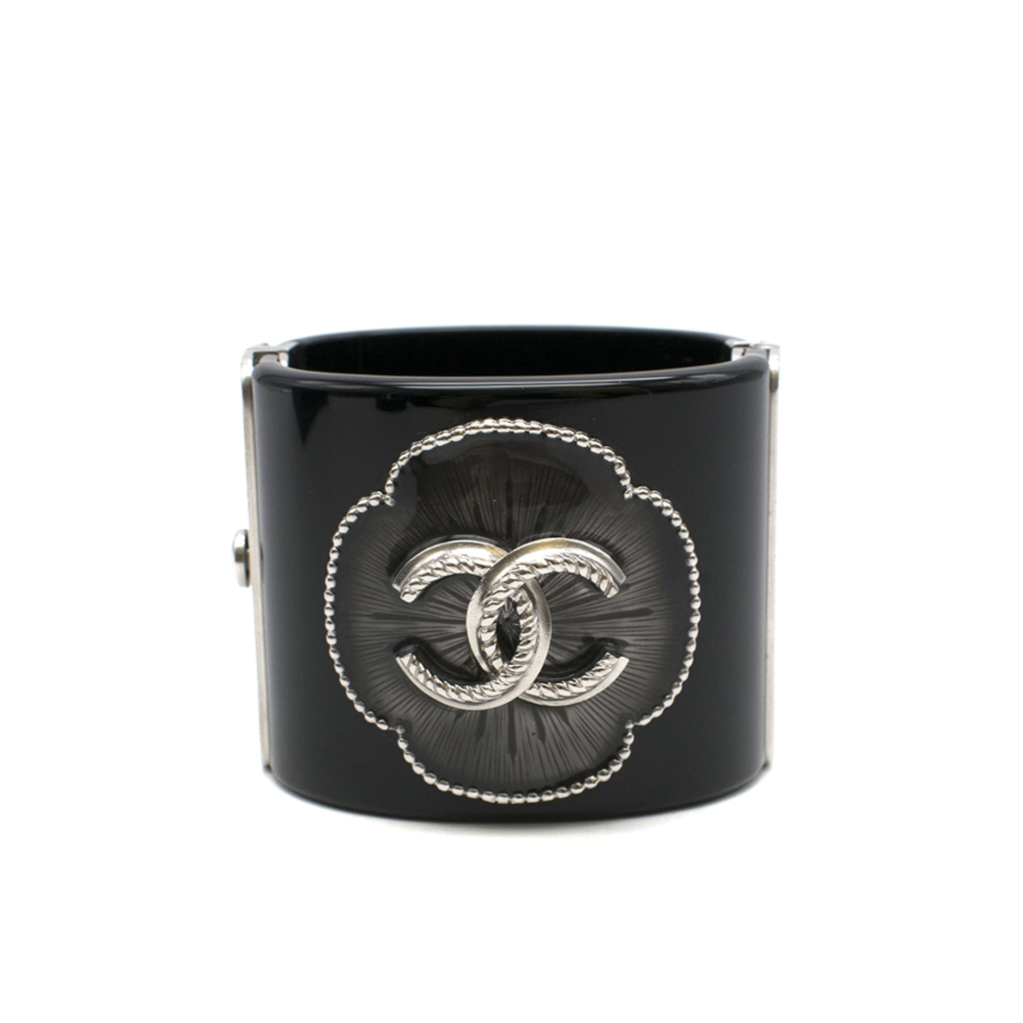 View full screen - View 1 of Lot 174. CHANEL | BLACK PERSPEX CUFF WITH A RESIN FILLED CAMELIA STUDDED FLORAL OUTLINE AND ANTHRACITE TONE HARDWARE AND CC EMBELLISHMENT, 2015.