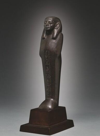 View 3. Thumbnail of Lot 66. AN EGYPTIAN BROWN SERPENTINE USHABTI OF NEDJEM-IB, LATE 12TH/13TH DYNASTY, CIRCA 1800-1640 B.C..