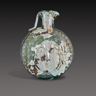 View 2. Thumbnail of Lot 1. A Roman Pale Green Mould-Blown Janiform Glass Flask, circa 1st/2nd century A.D..