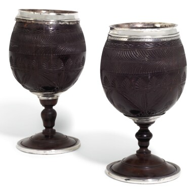 A PAIR OF GEORGE III SILVER MOUNTED CARVED COCONUT CUPS, THE MOUNTS UNMARKED, CIRCA 1790