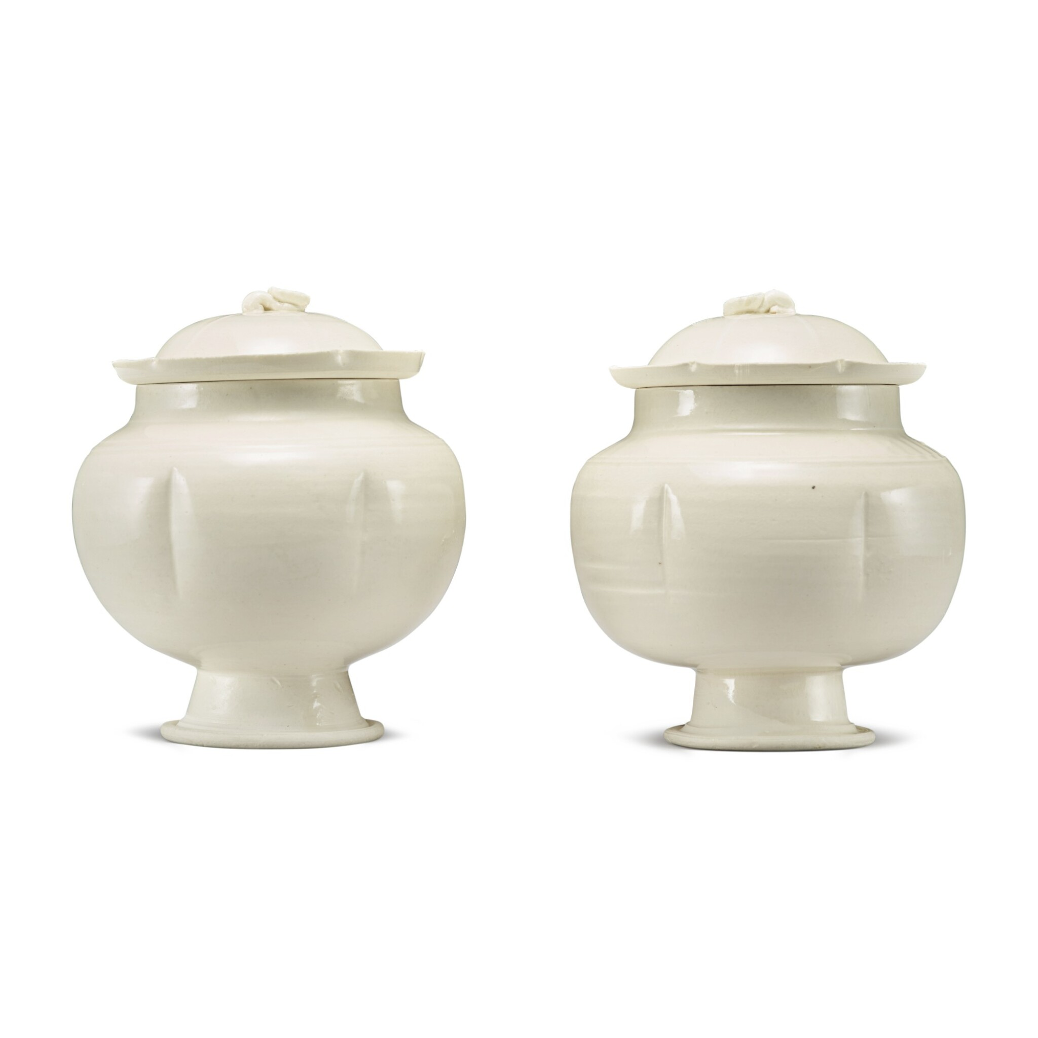 View full screen - View 1 of Lot 184. A pair of white-glazed footed jars and covers, Northern Song / Jin dynasty | 北宋 / 金 白釉瓜棱式高足蓋罐一對.