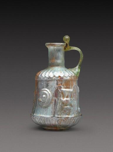 View 1. Thumbnail of Lot 4. A Roman Pale Green Mould-Blown Glass Flask, circa 1st century A.D..