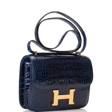 View 2. Thumbnail of Lot 3. Hermès Bleu Saphir Constance 18cm of Shiny Alligator with Gold Hardware.