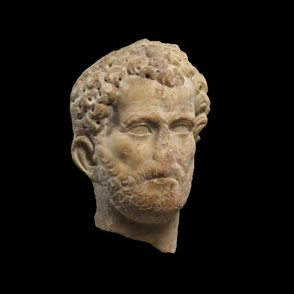 A ROMAN MARBLE RELIEF PORTRAIT HEAD OF A MAN, ANTONINE, PROBABLY EASTERN MEDITERRANEAN, CIRCA A.D. 140-150