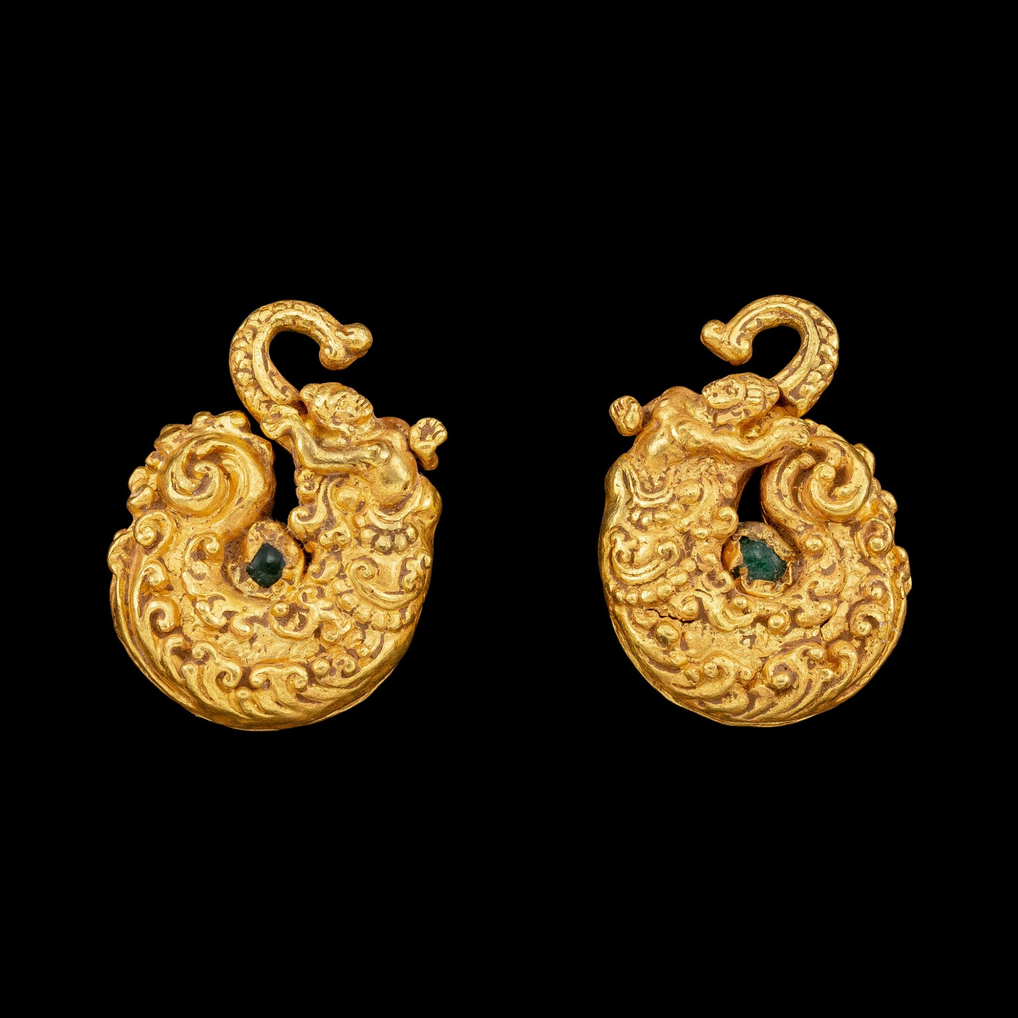 View full screen - View 1 of Lot 1025. A pair of gold repoussé 'Makara and human figure' earrings set with green glass beads Pre-Khmer, 8th century | 八世紀 前高棉時期 摩羯神像紋金耳飾一對.