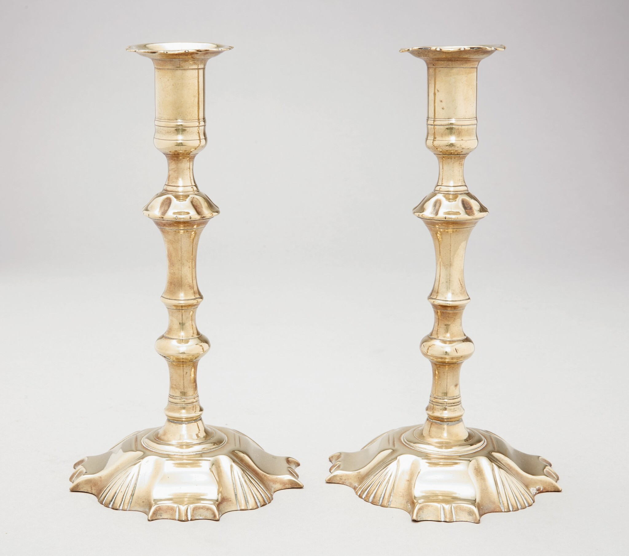 View 1 of Lot 1109. PAIR OF CHIPPENDALE CAST-BRASS PETAL-BASE CANDLESTICKS, ENGLAND, CIRCA 1770.