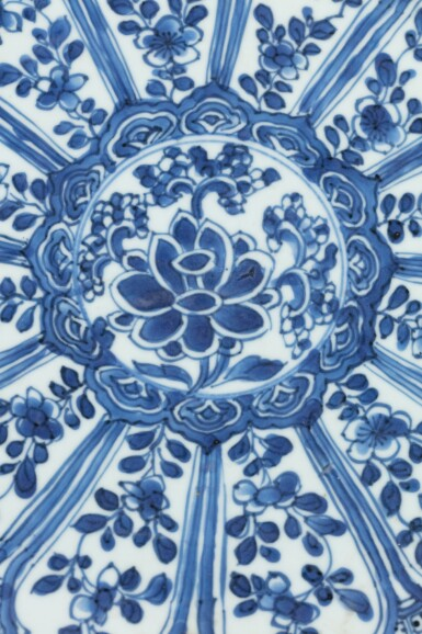 View 3. Thumbnail of Lot 379. A foliate 'floral' blue and white charger, China, Qing Dynasty, Kangxi period.