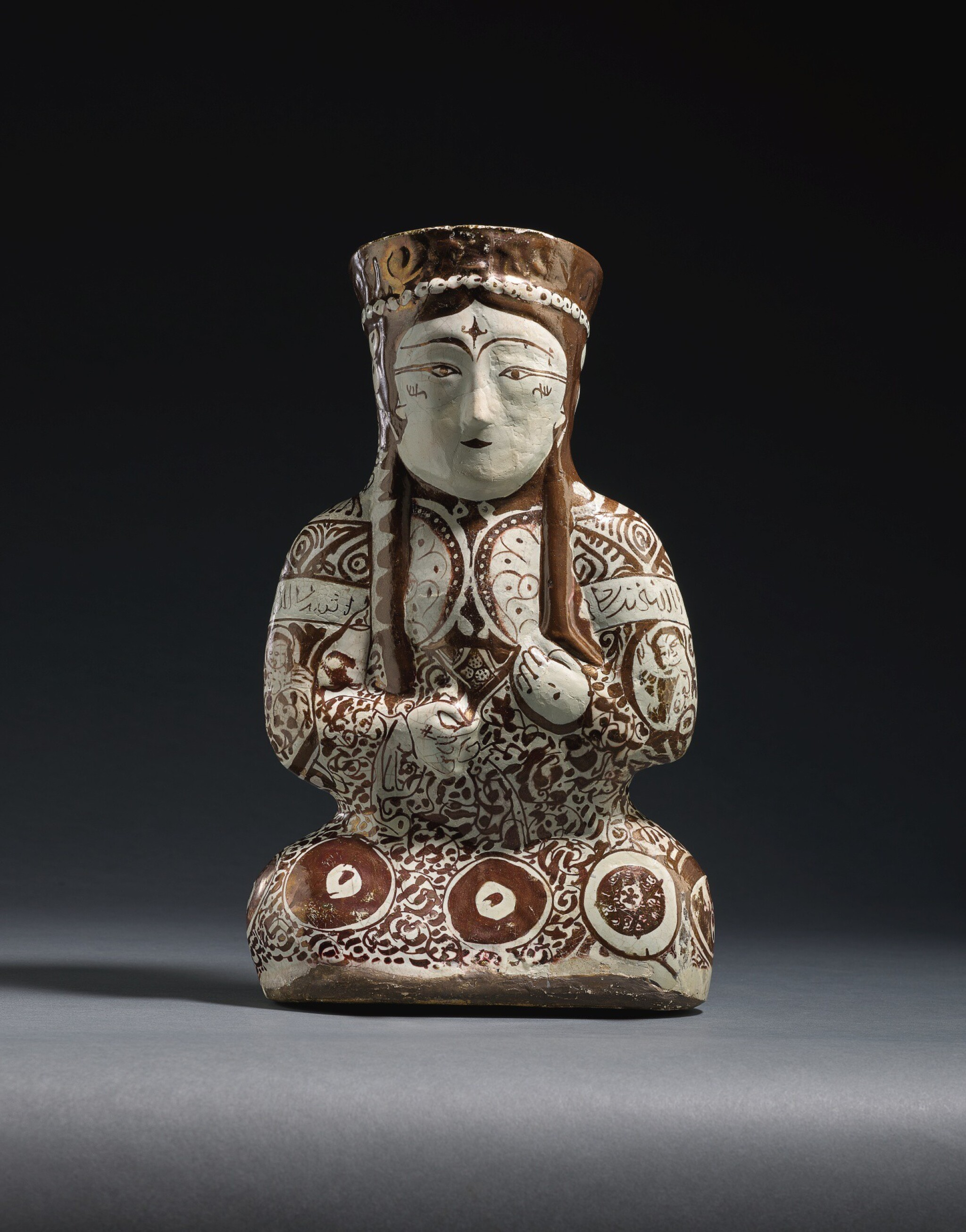 View full screen - View 1 of Lot 212. A KASHAN LUSTRE POTTERY VESSEL IN THE FORM OF A SEATED FEMALE RULER, PERSIA, 12TH/13TH CENTURY .