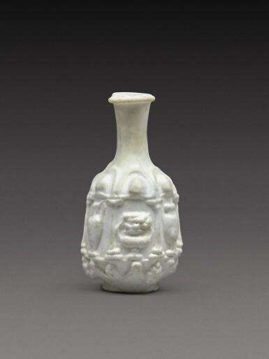 View 1. Thumbnail of Lot 7. A Roman Opaque White Mould-Blown Glass Flask, circa 1st century A.D..