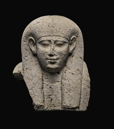 AN EGYPTIAN LIMESTONE SARCOPHAGUS MASK, 30TH DYNASTY/EARLY PTOLEMAIC PERIOD, CIRCA 250-200 B.C.