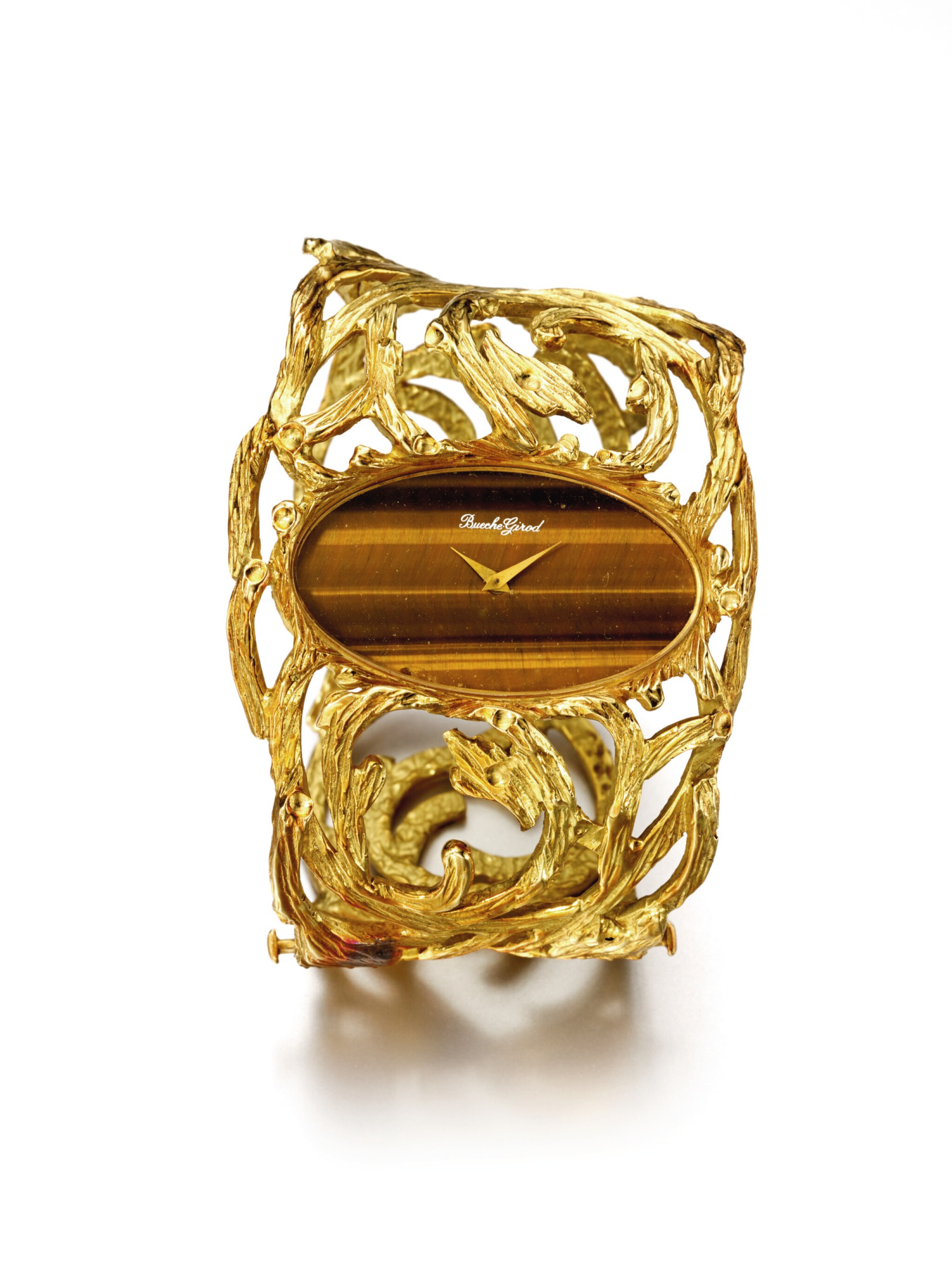 View full screen - View 1 of Lot 48. BUECHE GIROD | AN UNUSUAL YELLOW GOLD CUFF WATCH WITH TIGER'S EYE DIAL CIRCA 1975.