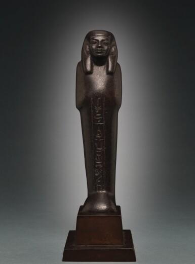 AN EGYPTIAN BROWN SERPENTINE USHABTI OF NEDJEM-IB, LATE 12TH/13TH DYNASTY, CIRCA 1800-1640 B.C.