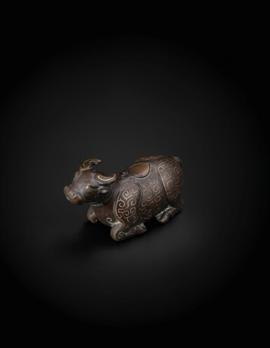 View 1. Thumbnail of Lot 48. A finely cast gold and silver inlaid archaistic 'recumbent buffalo' waterpot Yuan Dynasty -Ming Dynasty, 13th-15th century   元至明 十三至十五世紀 銅錯金銀臥牛水注.