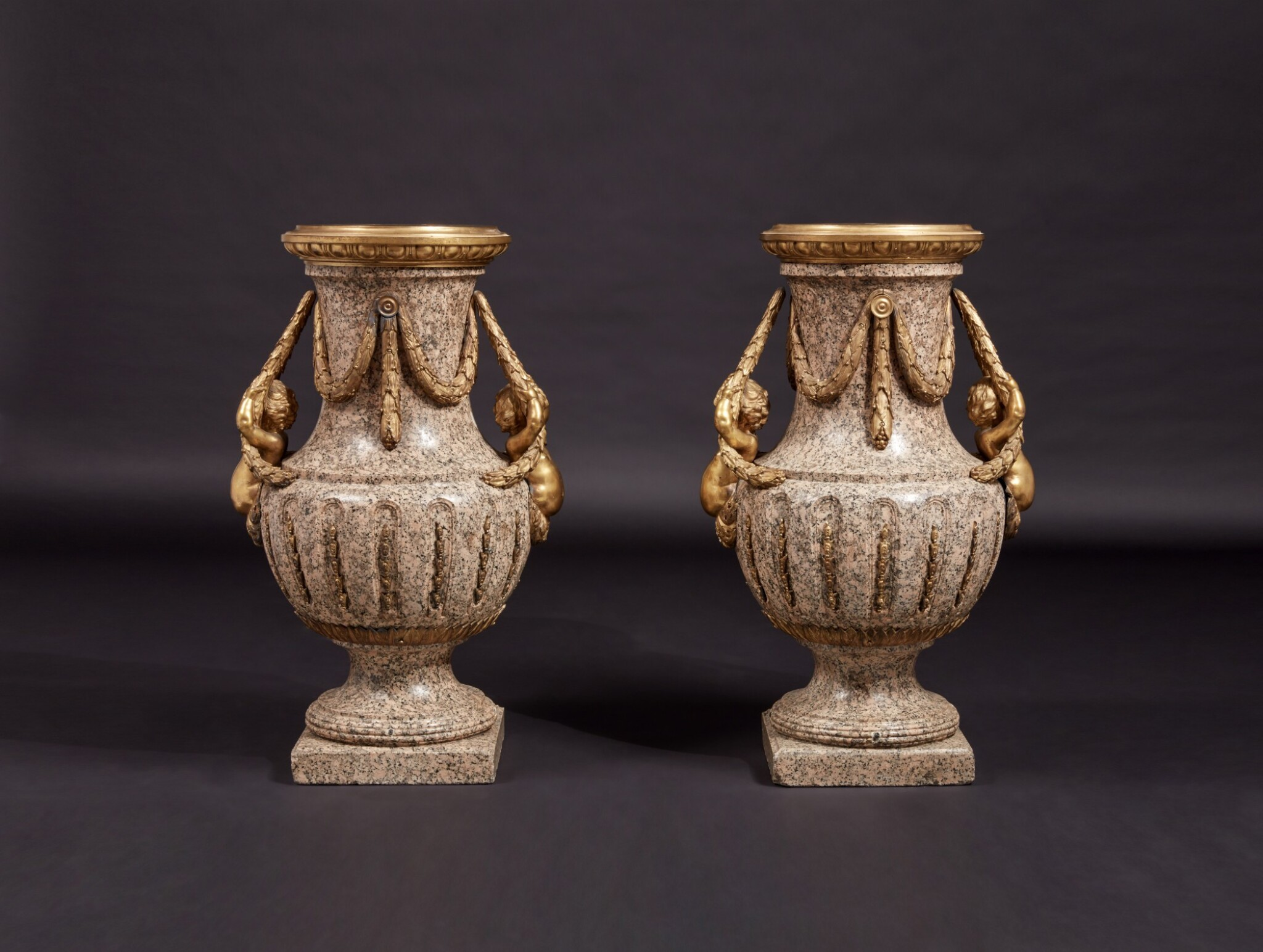 View full screen - View 1 of Lot 57. A Monumental Pair of Gilt Bronze-Mounted Pink Granite Vases, the Mounts Circa 1840 After Designs by Jean-Louis Prieur or Jean-François Forty; the Vases Possibly Late 18th Century.