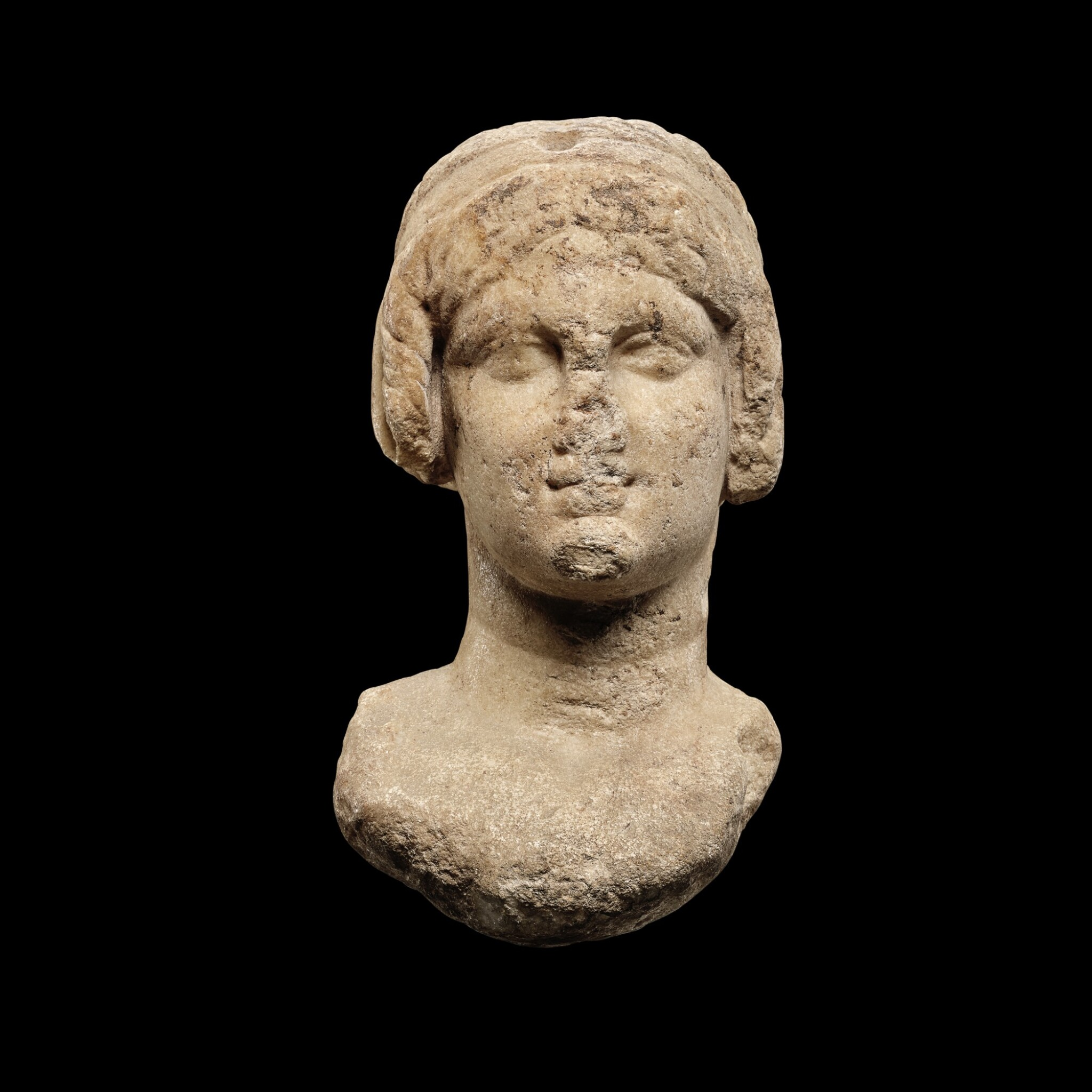 View 1 of Lot 62. A Ptolemaic Marble Head of a Queen in the guise of Isis, circa 2nd Century B.C..
