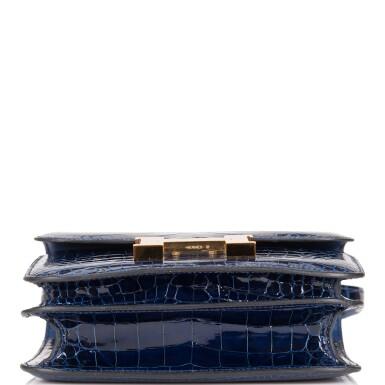 View 5. Thumbnail of Lot 3. Hermès Bleu Saphir Constance 18cm of Shiny Alligator with Gold Hardware.