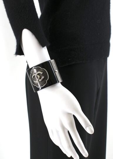 View 10. Thumbnail of Lot 174. CHANEL | BLACK PERSPEX CUFF WITH A RESIN FILLED CAMELIA STUDDED FLORAL OUTLINE AND ANTHRACITE TONE HARDWARE AND CC EMBELLISHMENT, 2015.