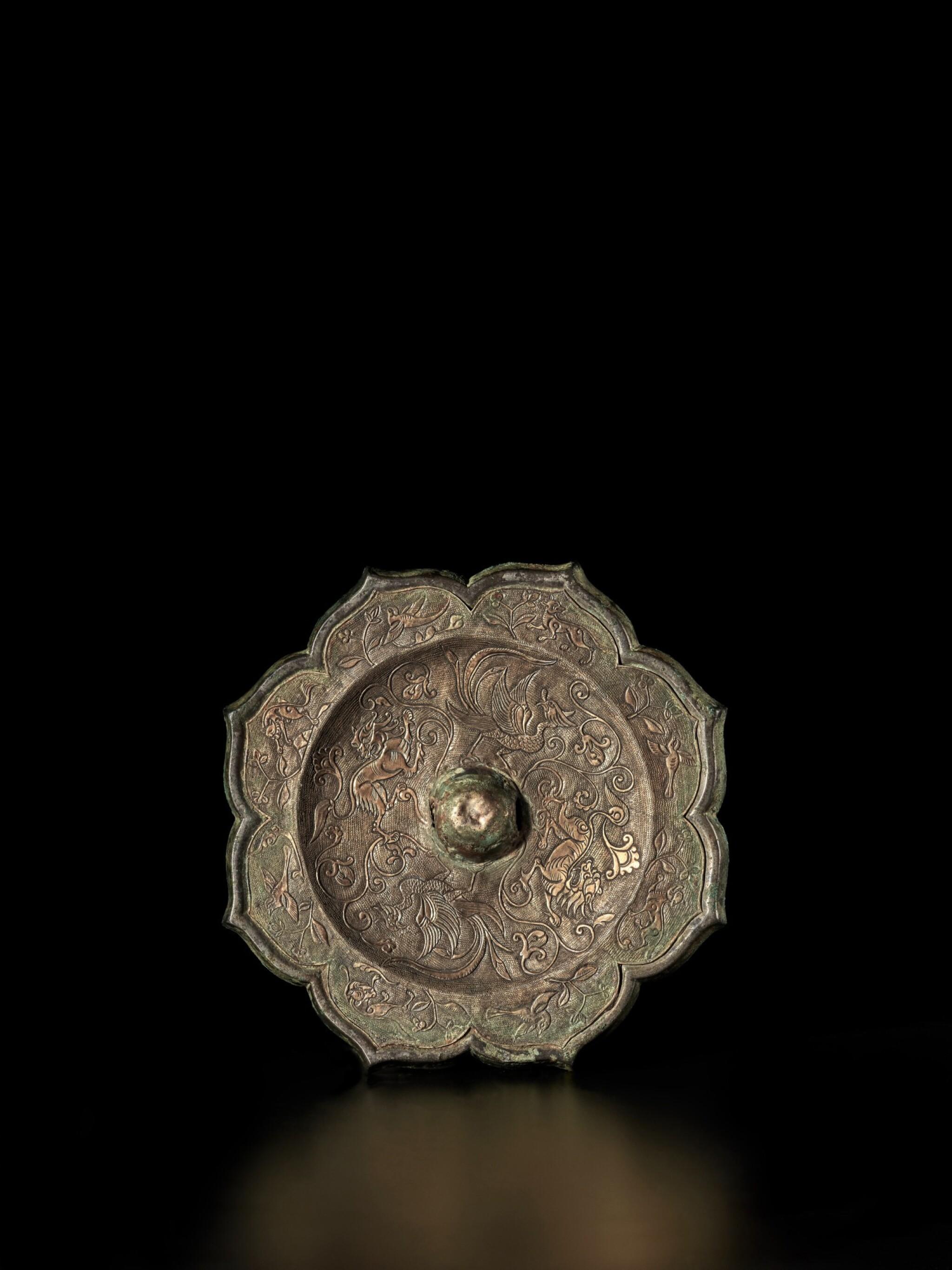 View full screen - View 1 of Lot 48. A rare gilt-silver-inset bronze mirror, Tang dynasty | 唐 嵌銀鎏金雙鳳狻猊紋銅鏡.