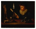 Boy behind a table with statuettes reading by candlelight